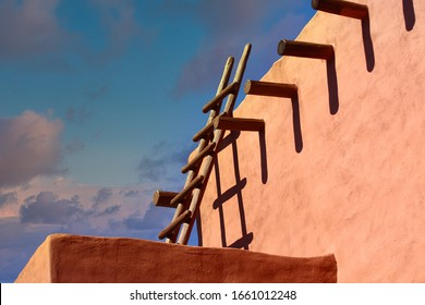 An old wood ladder leaning on a red adobe wall under blue skies