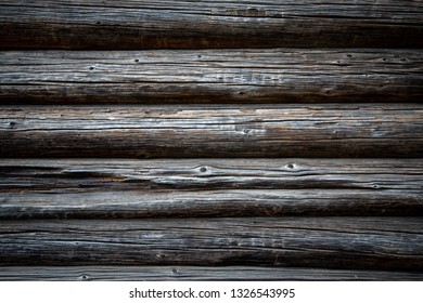 Old wood log background with cracks and lines. Light in the middle with space for copy, dark at the sides. Wall of house.