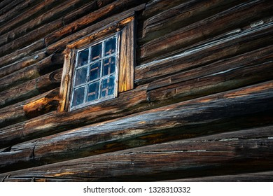 Old wood log background with cracks and lines. Windows on wall of house.