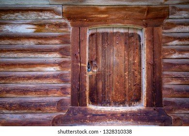 Old wood log background with cracks and lines. Door in the middle. Wall of house.