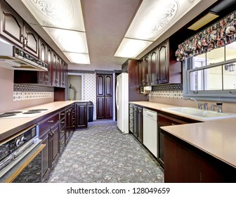 Old wood narrow kitchen with carpet and curtains.