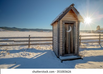 Old wood outhouse in winter with sun star