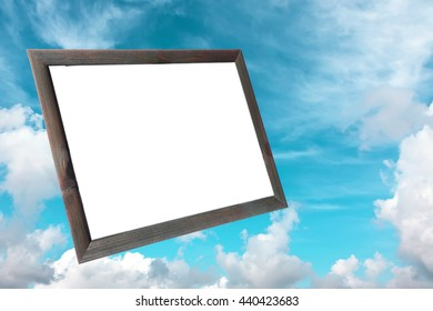 Old wood photo frame with white copy space inside on the background of the blue sky with fluffy white clouds. Blank space for any text (advertising, announcement). Toned colors