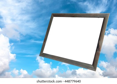 Old wood photo frame with white copy space inside on the background of the blue sky with fluffy white clouds. Blank space for any text (advertising, announcement)