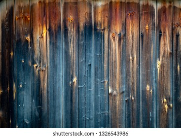 Old wood plank background with cracks and lines. Light in the middle with space for copy, dark at the sides. Wall of house.