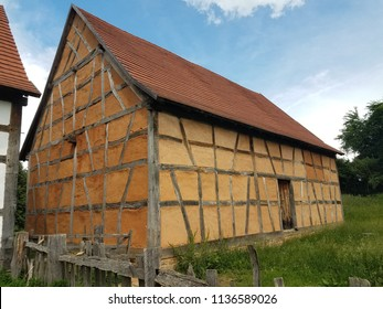 old wood and plaster building and green grass