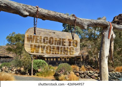 "old wood signboard with text "" welcome to wyoming"" hanging on a branch"