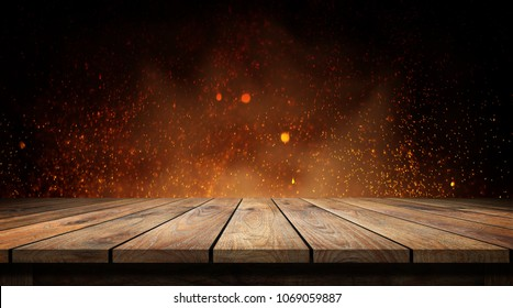 Old wood table with flame effect on dark background.