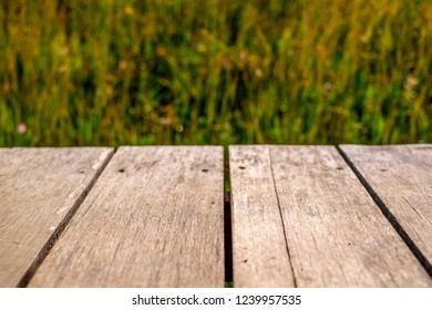 Old wood table foreground texture pattern with blurred green grass