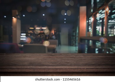 Old wood table in front of blurred cafe restaurant background, copy space can be placed your product