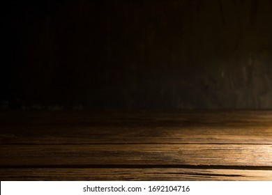 Old wood table on dark background.