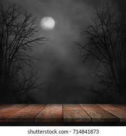 Old wood table and silhouette dead tree at night for Halloween background.