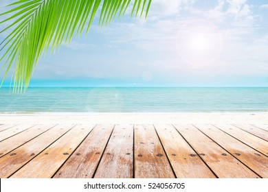 old wood table top on blurred beach background with coconut leaf. Concept Summer, Beach, Sea, Relax.