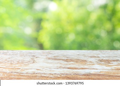 Old wood tabletop on natural green bokeh blackground in shinny summer day ready for display your product