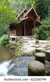 Old wood Thai style temple with ruin stone walk path in foreground and green tropical forest in background over flowing long exposure small waterfall