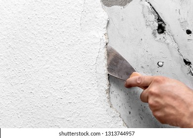Old woodchip wallpaper is removed or scraped off the wall with a spatula or painter's spatula