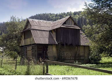 Old wooden abandoned house with boarded up windows against the background of the green Carpathian Mountains