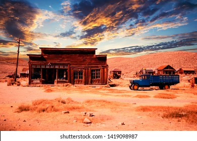 old wooden abandoned house with car in the desert at sunset