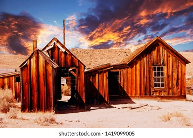 old wooden abandoned house in the desert at sunset
