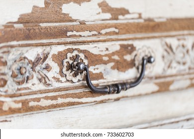 Old wooden antique chest of drawers with metal handles closeup.