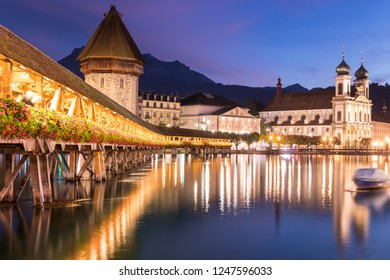 Old wooden architecture called Chapel Bridge in Luzern or Lucerne, Switzerland during sunset and twilight