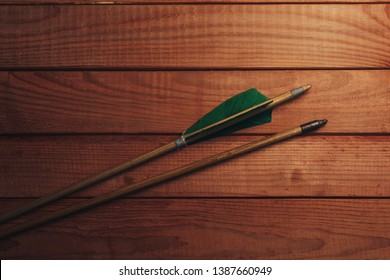 Old wooden arrow. Beautiful wooden table background. Medieval weapons are handmade.