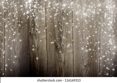 Old wooden background with falling snow flakes