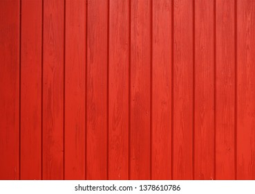 Old wooden background painted with red paint with a texture of cracks and scratches. Red background