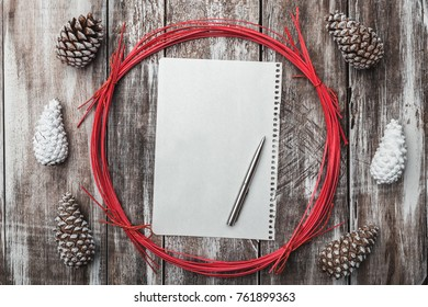 Old wooden background. Pine cones. Red decorative circle. Space for message Xmas, Christmas and New Year. Letter to Santa.Xmas and Happy New Year composition. Flat lay, top view