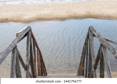 Old wooden banister on the beach, look through the stair way with banister on the side and wind blow the sea surface
