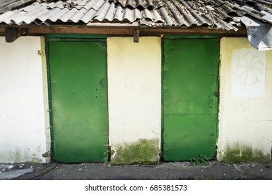Old wooden bar with grey roof and many green doors.