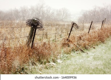 An old wooden and barbed wire fence in the country is getting lightly dusted in snow flurries