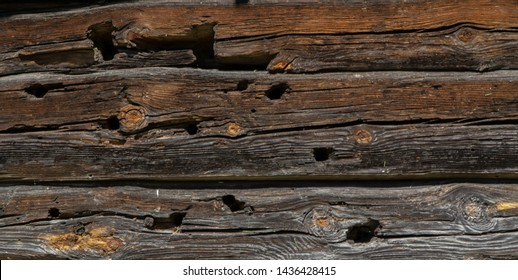 Old wooden barn wall with bullet traces