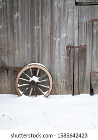 Old wooden barn wall with an old wooden cartwheel standing in front of it. With snow on cartwheel and in front of the barn