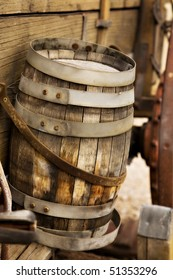 An old wooden barrel in attached to the side of a wagon from the old west.