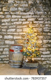 Old wooden barrel and illuminated christmas tree in front of limestone wall