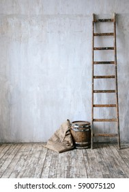 Old wooden barrel, sack cloth and ladder with concrete grey wall and wooden floor. Grunge vintage interior of loft, cellar, basement or studio. Mock up with space for text