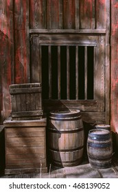 Old wooden barrels and boxes next to the door of a western shed