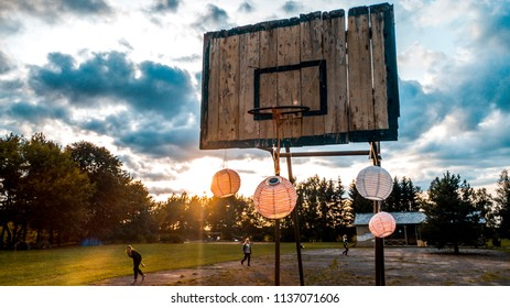 Old wooden basketball board and Chinese lanterns in a grass field in front of the forest  during sunset in Lithuanian Summer Camp