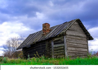 An old wooden bath house on the outskirts of the village. Against the background of the cloudy sky. Concept: old buildings, country style, vintage and antiques.