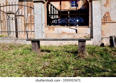 Old wooden bench in an abandoned place. An unusual bench in an ordinary place. An old wooden bench against the backdrop of a ruined abandoned building.