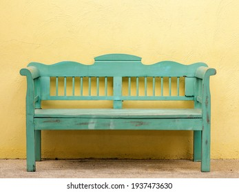 The old wooden bench in green color in front of the yellow wall. Wooden 2 seater garden bench. The green wooden bench and the yellow wall. Garden or outdoor furniture.