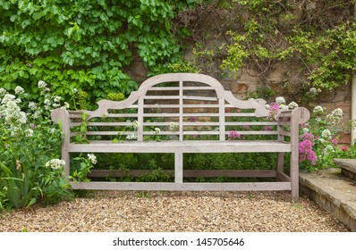 Old wooden bench situated in a landscaped garden.