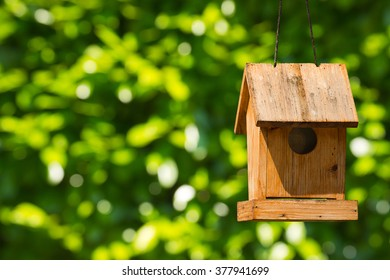 Old wooden birdhouse hanging with ropes. On a green blurred background
