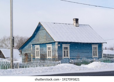 Old wooden blue house in village. Farmhouse in Belarus. View of rustic ethnic house, rural landscape in winter day