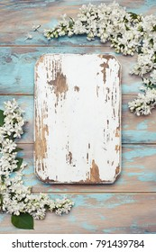 Old wooden board and white lilac flowers on blue rustic wooden background. Spring flowers composition with copy space