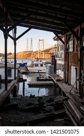 Old wooden boat dock, boats, water and bridge.