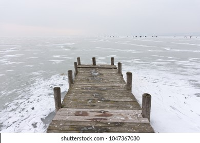 Old wooden boat dock on the frozen Lake Neusiedl in Weiden with some snow on the ice surface and people ice skating on the far horizon in the background.