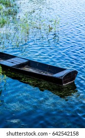 The old, wooden boat isolated on the blue - lake background