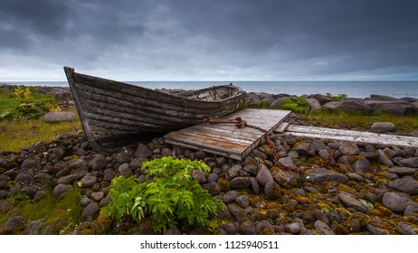 Old wooden boat on dry land by the seaside on southwest coast of Iceland.
